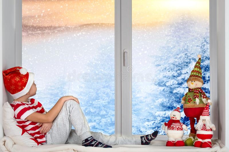 Merry Christmas and happy holidays!Baby boy sitting on window and looking at the snowfall in the woods.Room decorated on Christmas stock images