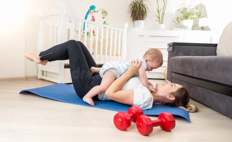 Cute baby boy sitting on young mother exercising on fitness mat at home. Baby boy sitting on young mother exercising on fitness mat at home stock photo