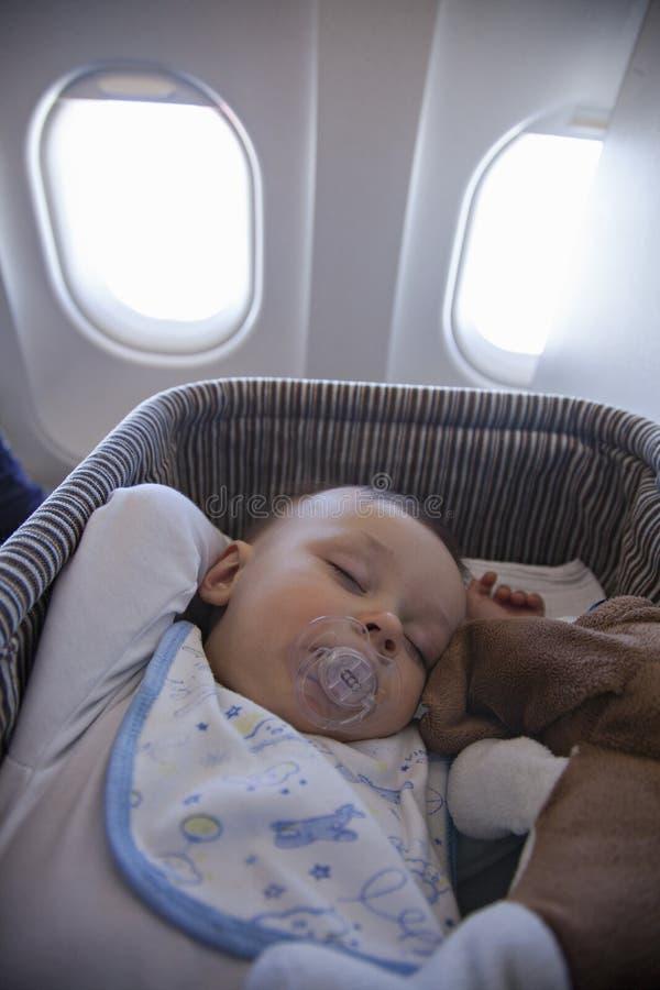 Baby Boy Sleeping In Bassinet On Airplane. Adorable Baby Boy Sleeping In Special Bassinet On Airplane stock image