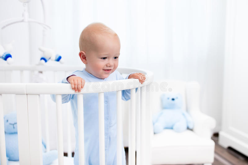 Baby boy standing in bed in white nursery. Funny little baby standing in round modern bed with mobile in white nursery with window. Infant boy in blue pajamas stock images