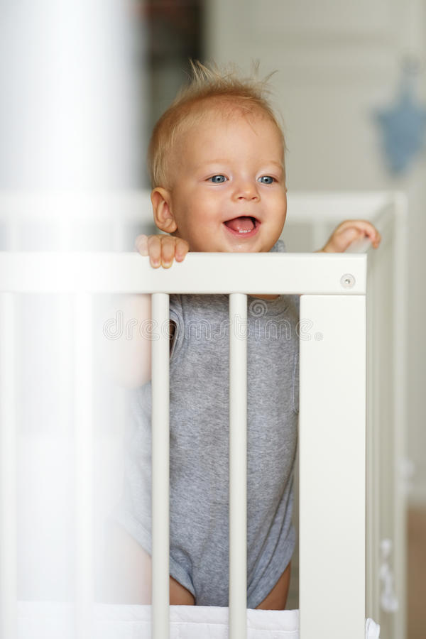Baby boy standing in crib. Baby boy with blue eyes standing in crib stock images