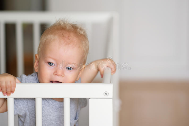 Baby boy standing in crib. Baby boy with blue eyes standing in crib royalty free stock photo