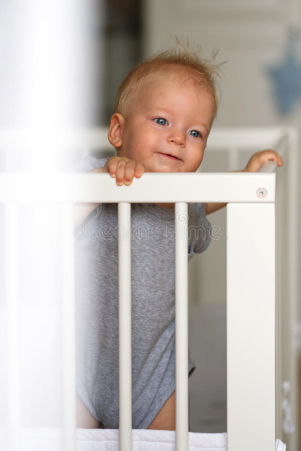 Baby boy standing in crib. Baby boy with blue eyes standing in crib royalty free stock images