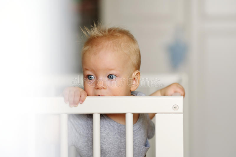 Baby boy standing in crib. Baby boy with blue eyes standing in crib royalty free stock photography