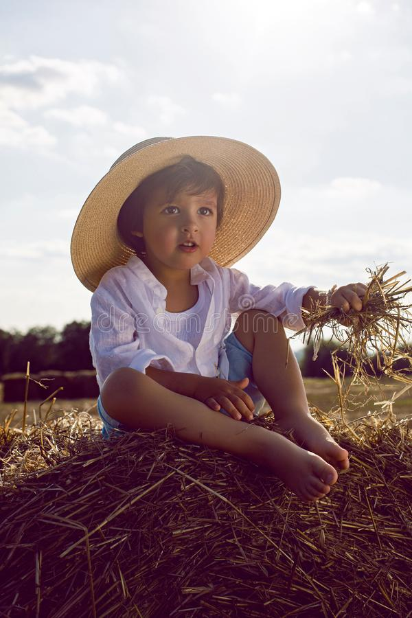 Baby boy in straw hat and blue pants sitting on a haystack in a field royalty free stock images