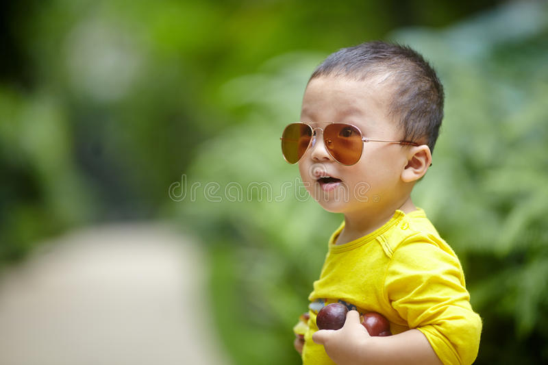 Baby boy with sunglasses. Adorable baby boy with sunglasses outdoors at sunny summer day stock photos