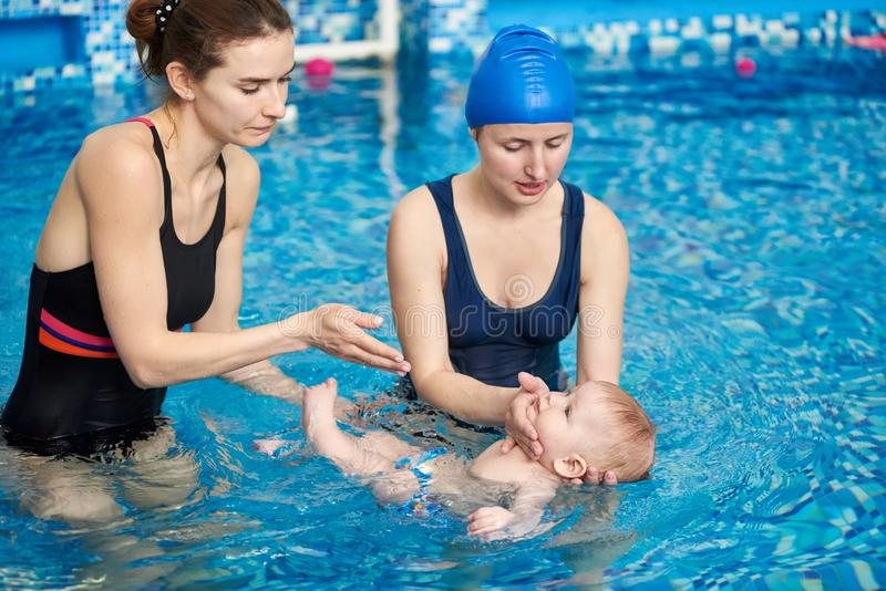 Baby boy swimming with mother and instructor in paddling pool. Coach showing precautions for safe swimming with baby stock photos