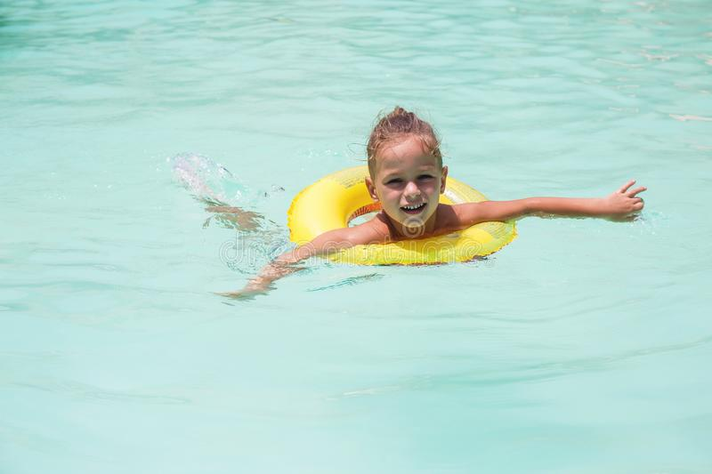 Baby boy is swimming in the pool. With a lifebuoy royalty free stock image