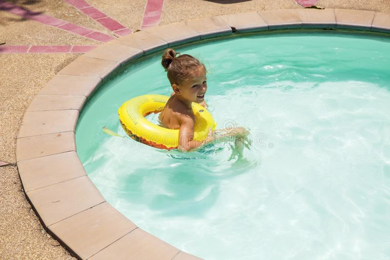 Baby boy is swimming in the pool. With a lifebuoy royalty free stock photography