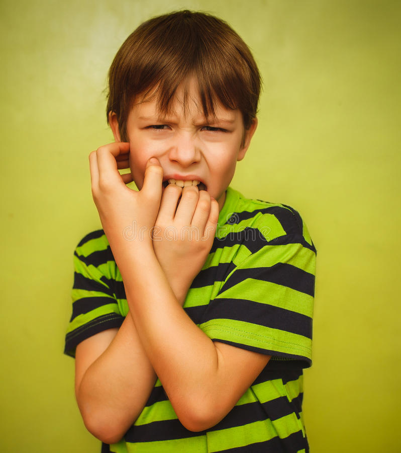 Baby boy teenager feels fear anxiety bad habit. Baby boy teenager feels fear anxiety anxiety bad habit of biting your nails on a green background expression of stock photo