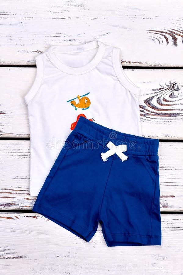 Baby boy textile summer clothes. Infant boy white sleeveless cartoon t-shirt, blue shorts on white wooden background, top view. New kids apparel on sale stock images