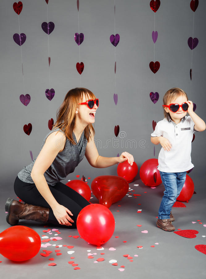 Baby boy toddler with mother in studio wearing funny glasses smiling laughing having fun royalty free stock photography