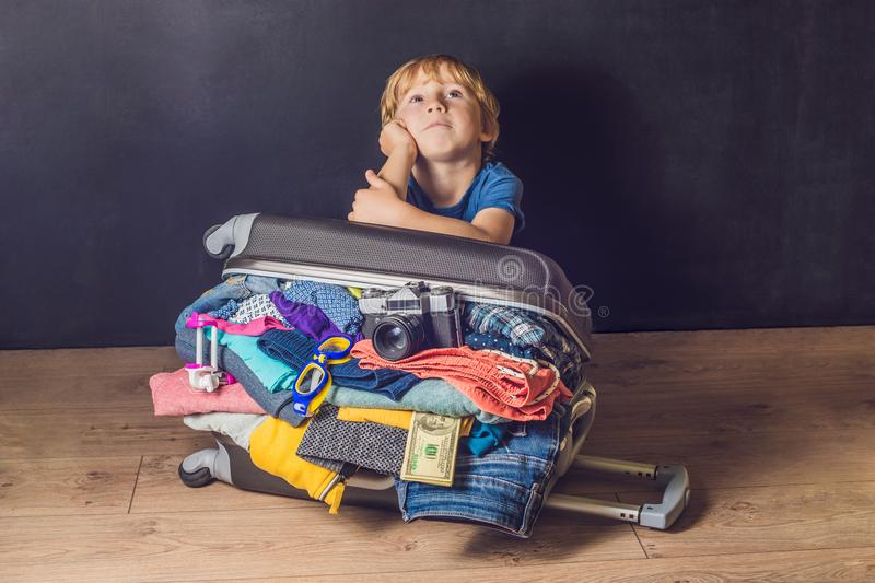 Baby boy and Travel Suitcase. Kid and Luggage Packed for Vacation Full of Clothes, Child and Family Trip stock photo
