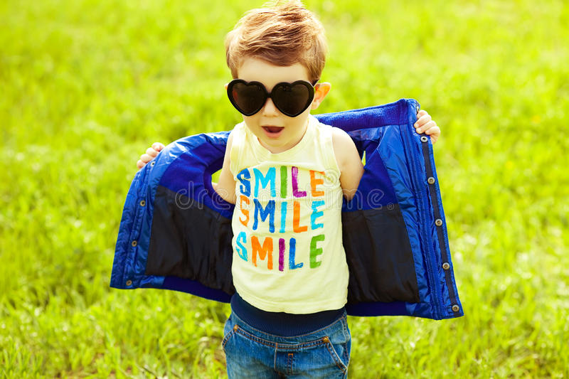 Baby boy in trendy sunglasses. Eyewear concept. Stylish baby boy with ginger (red) hair in trendy sunglasses (heart form) and blue jacket standing in the park stock photography