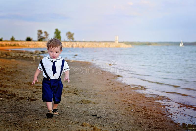 Toddler boy walking on beach in sailor outfit. Baby boy walking on the beach near a lake stock photos