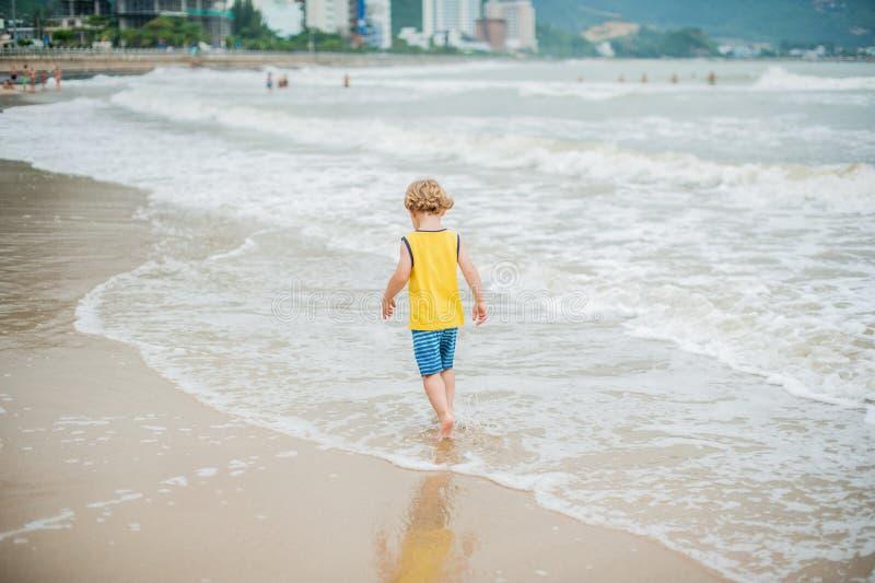 Baby boy walking on the sandy beach near the sea. Cute little kid at sand tropical beach. stock photography