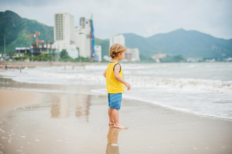 Baby boy walking on the sandy beach near the sea. Cute little kid at sand tropical beach. stock image