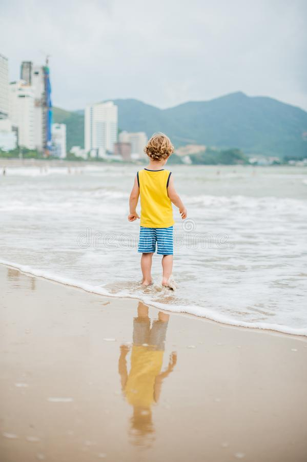 Baby boy walking on the sandy beach near the sea. Cute little kid at sand tropical beach. stock photos