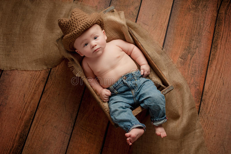 Baby Boy Wearing a Cowboy Hat. A four month old baby boy wearing a crocheted cowboy hat. He is lying in a wooden crate lined with burlap. Shot in the studio on a royalty free stock photos
