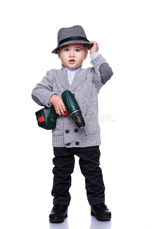 Baby boy wearing a hat holding an electrical drill stock photos