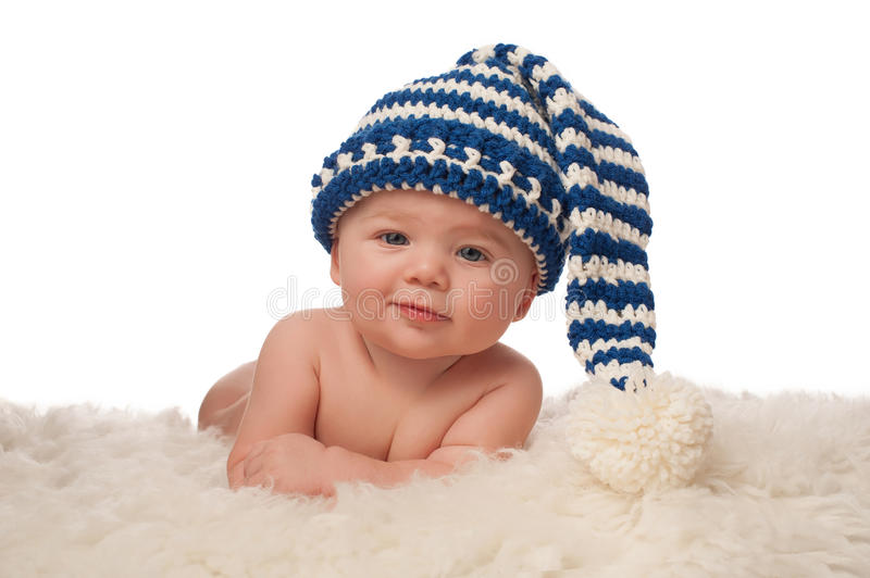 Baby Boy Wearing a Stocking Cap. A 4 month old baby boy wearing a blue and cream colored, crocheted stocking cap. He has a slight grin and is looking at the royalty free stock photography