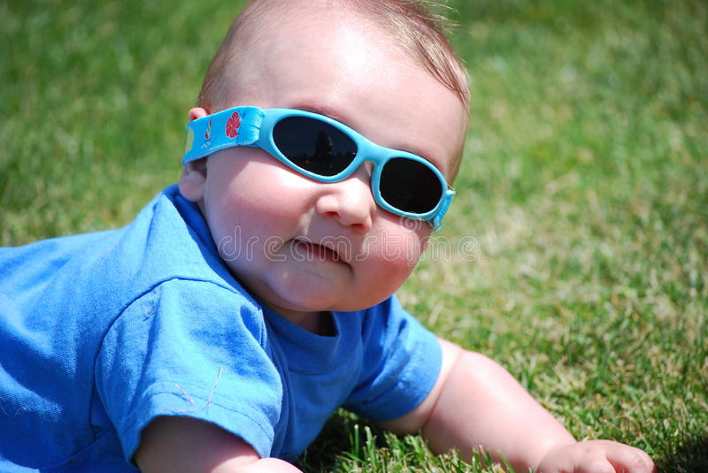 Baby boy wearing sunglasses laying on grass. A baby boy laying in a field of grass wearing sunglasses royalty free stock images