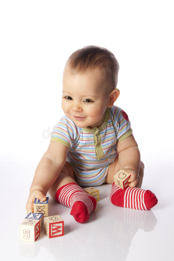 Baby boy with wooden blocks stock images