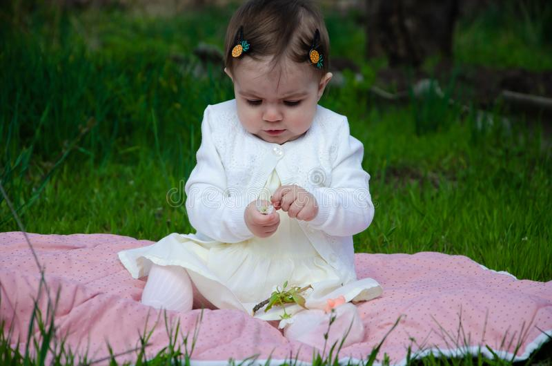 Baby in bright clothes on a pink plaid on green grass in the park stock photo