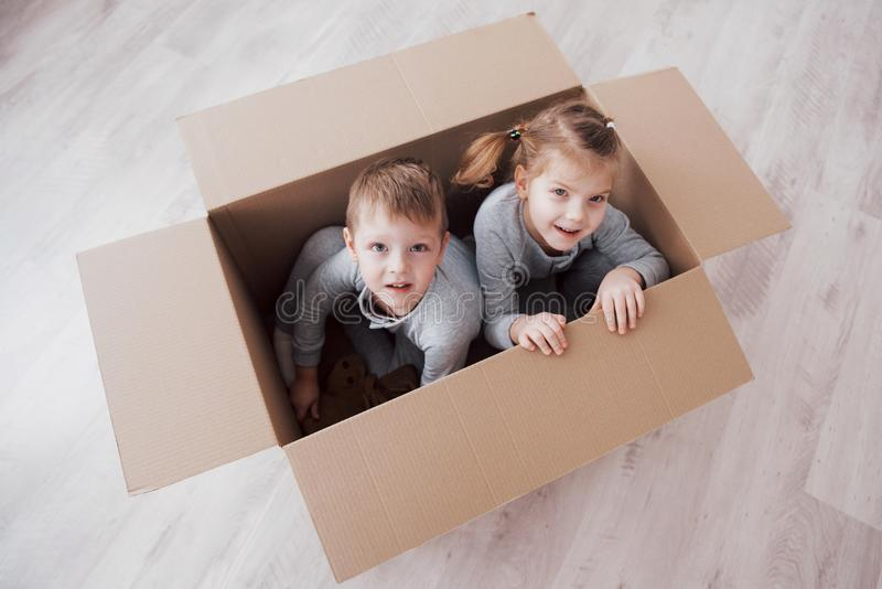 Baby brother and child sister playing in cardboard boxes in nursery.  royalty free stock photo