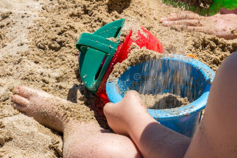 Baby on brown sand beach playing with beach bucket and shovel. royalty free stock image