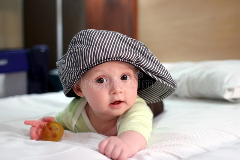 Baby in cap. Baby boy on bed in oversized cap royalty free stock photo