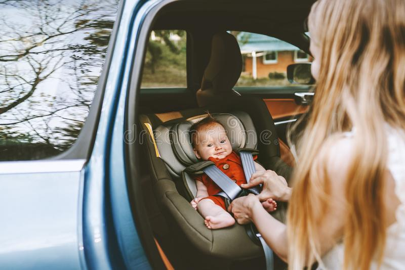 Baby in car mother fastens belts of safety car seat royalty free stock images