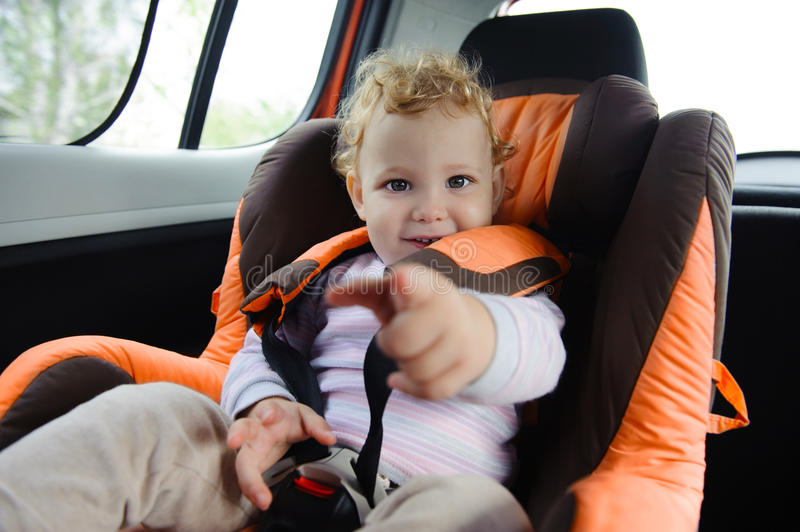 Baby in car seat. Cute baby enjoying a road trip in a baby car seat stock photography