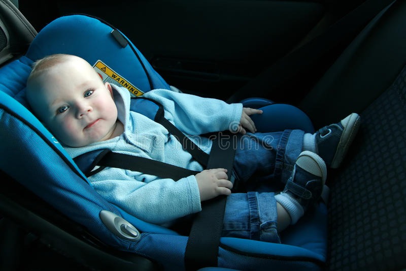 Baby in car seat. 7 months old baby boy in a safety car seat. Safety and security stock images