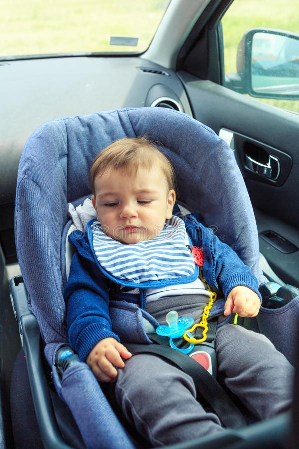 Baby car seat for safety. baby boy in safety car seat with safety belt locked protection. Protection in the car stock photography