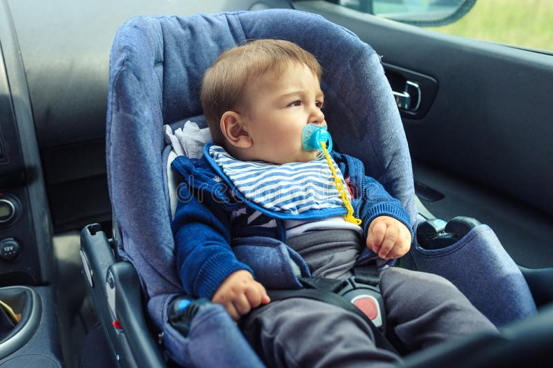 Baby car seat for safety. Happy Boy sitting in a car in safety chair. Protection in the car royalty free stock image