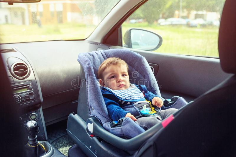 Baby car seat for safety. Smiling Boy sitting in a car in safety chair. Protection in the car royalty free stock photography