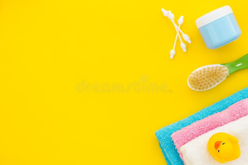 Baby care. Bath cosmetics and accessories for child. Shampoo, gel, cream, comb, yellow rubber duck on yellow background stock images
