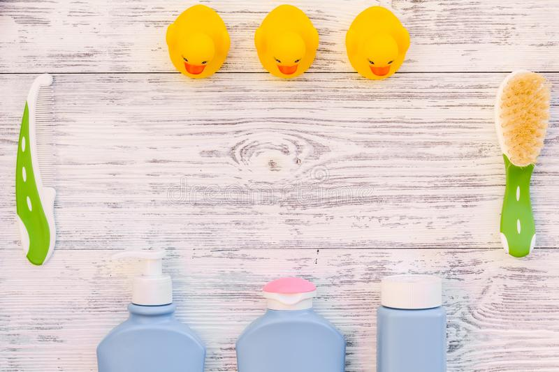 Baby care. Bath cosmetics and accessories for child. Shampoo, gel, cream, teeth brush, comb, yellow rubber duck on grey royalty free stock image