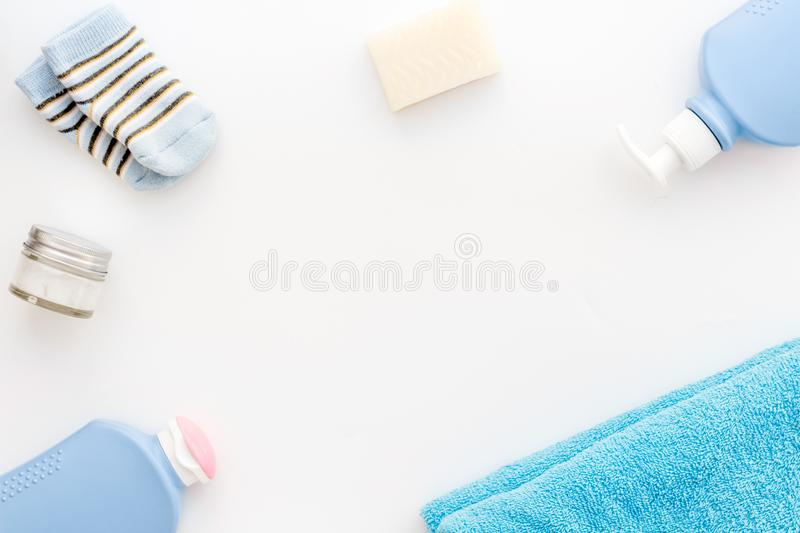 Baby care. Bath cosmetics and accessories for child. Shampoo, gel, cream, towel, socks on white background top view copy stock image