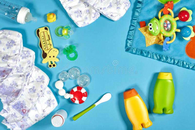 Baby care with bath set. Nipple, toy, diapers, shampoo on blue background top view mockup stock photo