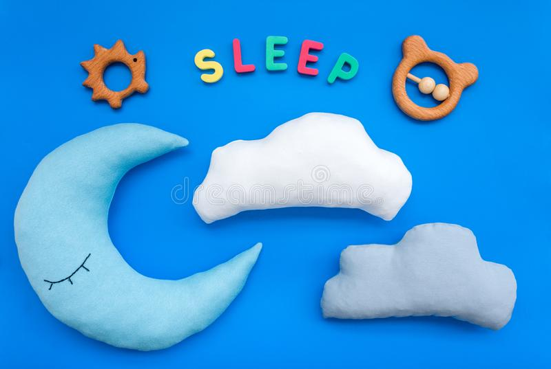 Baby care concept with moon pillow, clouds, sleep copy and toy for sleep of newborn on blue background top view stock photos