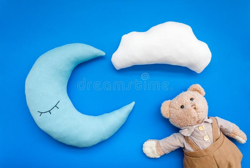 Baby care concept with moon pillow, clouds, teddy bear and toy for sleep of newborn on blue background top view stock image