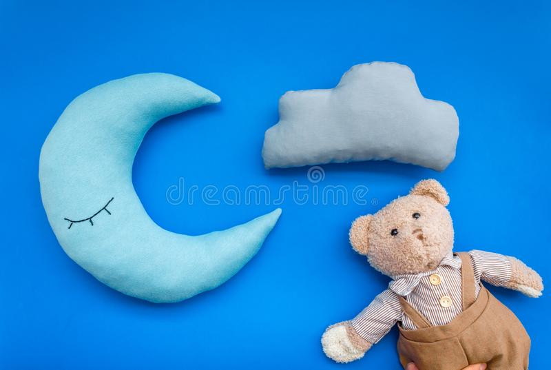 Put baby into bed with moon pillow, clouds, teddy bear and toy on blue background top view stock image