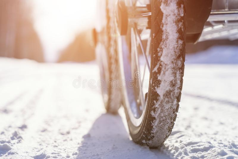 Baby carriage with inflatable wheels on the winter snow road under bright sun at light day stock images