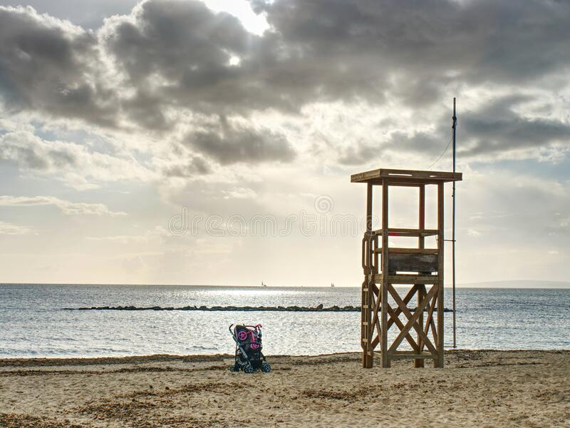 Baby carriage standing under lifeguard tower stock photography