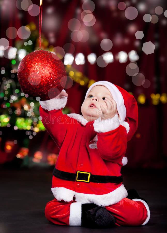 Baby catching Christmas ball royalty free stock image