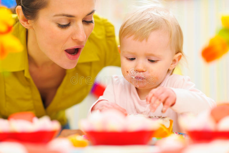 Baby celebrating first birthday with mom. Baby girl celebrating first birthday with mom stock photo