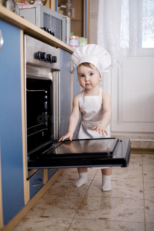 Baby chef cooks in the oven food stock image