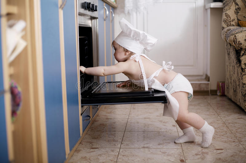 Baby chef cooks in the oven food stock photography